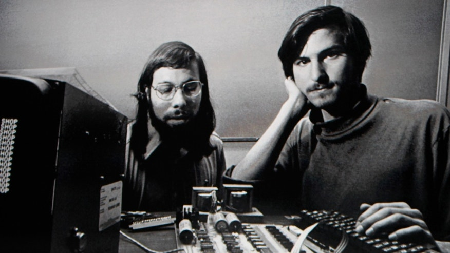 File photo - Steve Jobs stands beneath a photograph of him and Apple-co founder Steve Wozniak from the early days of Apple during the launch of the iPad in San Francisco, Calif., Jan. 27, 2010. (REUTERS/Kimberly White)