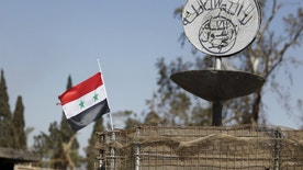 "A Syrian national flag flutters next to the Islamic State's slogan at a roundabout where executions were carried out by ISIS militants in the city of Palmyra, in Homs Governorate, Syria April 1, 2016. REUTERS/Omar Sanadiki SEARCH ""PALMYRA SANADIKI"" FOR THIS STORY. SEARCH ""THE WIDER IMAGE"" FOR ALL STORIES - RTSD6R1"