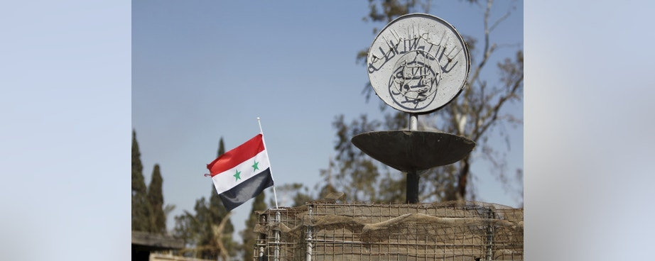 """A Syrian national flag flutters next to the Islamic State's slogan at a roundabout where executions were carried out by ISIS militants in the city of Palmyra, in Homs Governorate, Syria April 1, 2016. REUTERS/Omar Sanadiki SEARCH """"PALMYRA SANADIKI"""" FOR THIS STORY. SEARCH """"THE WIDER IMAGE"""" FOR ALL STORIES - RTSD6R1"""