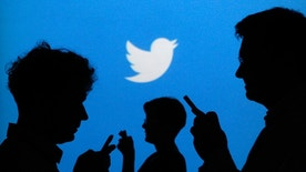 People holding mobile phones are silhouetted against a backdrop projected with the Twitter logo in this illustration picture taken in  Warsaw September 27, 2013. Twitter Inc, the eight-year-old online messaging service, gave potential investors their first glance at its financials on Thursday when it publicly filed its IPO documents, setting the stage for one of the most-anticipated debuts in over a year. Picture taken September 27.  REUTERS/Kacper Pempel (POLAND - Tags: BUSINESS TELECOMS LOGO) - RTR3FL8C