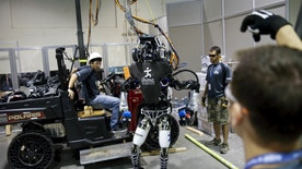 "The Team IHMC Robotics Atlas ""Running Man"" robot built by Boston Dynamics is readied in the team garage during the finals of the Defense Advanced Research Projects Agency (DARPA) Robotic Challenge in Pomona, California June 6, 2015. Twenty-four teams are competing to win a portion of a $3.5 million prize by operating humanoid robots across a task and obstacle course.  REUTERS/Patrick T. Fallon - RTX1FEIK"