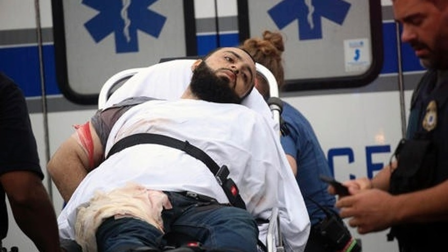 Ahmad Khan Rahami is taken into custody after a shootout with police Monday, Sept. 19, 2016, in Linden, N.J. Rahami was wanted for questioning in the bombings that rocked the Chelsea neighborhood of New York and the New Jersey shore town of Seaside Park. (Nicolaus Czarnecki/Boston Herald via AP)