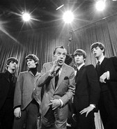 """** FOR USE AS DESIRED WITH BEATLES 45TH ANNIVERSARY ** In this Feb. 9, 1964 file photo, Ed Sullivan, center, stands with The Beatles during a rehearsal for the British group's first American appearance, on the """"Ed Sullivan Show,"""" in New York. From left:  Ringo Starr, George Harrison, Sullivan, John Lennon and Paul McCartney. The rock 'n' roll band known as """"The Fab Four"""" was seen by 70 million viewers. """"Beatlemania"""" swept the charts with twenty No.1 hits and more than 100 million records sold.  The Beatles broke up in 1970.  (AP Photo)"""