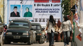 Women walk in front of a billboard for local elections in Indonesia's Aceh province in Banda Aceh November 24, 2006. Political campaigning kicks off across Indonesia's once rebellious Aceh province this week for landmark December 11 elections.  REUTERS/Tarmizy Harva (INDONESIA) - RTR1JNR2