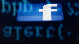 A Facebook logo on an Ipad is reflected among source code on the LCD screen of a computer, in this photo illustration taken in Sarajevo June 18, 2014.  Ireland's High Court on Wednesday asked the European Court of Justice (ECJ) to review a European Union-U.S. data protection agreement in light of allegations that Facebook shared data from EU users with the U.S. National Security Agency.   REUTERS/Dado Ruvic  (BOSNIA AND HERZEGOVINA - Tags: CRIME LAW BUSINESS POLITICS) - RTR3UHB1