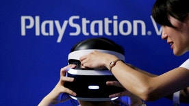 A hostess helps a woman to wear Sony's PlayStation VR headset at Tokyo Game Show 2016 in Chiba, east of Tokyo, Japan, September 15, 2016. REUTERS/Kim Kyung-Hoon/File Photo - RTSRVVS