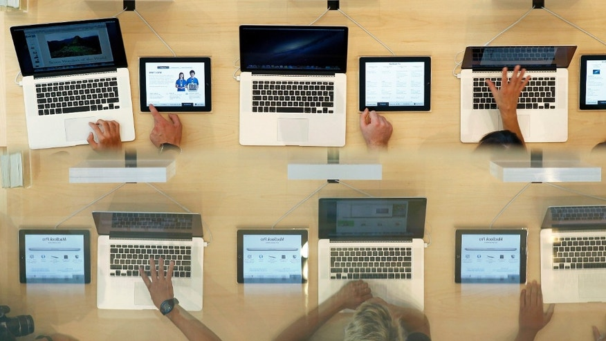 File photo - Customers look at MacBook Pros, during the official opening of the largest Apple shop in southern Europe, at Passeig de Gracia in Barcelona July 28, 2012. The bottom image is a reflection on a glass surface. (REUTERS/Albert Gea)