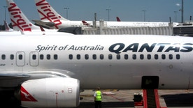 Virgin Australia aircraft can be seen behind a Qantas Airways Boeing 737-800 plane being inspected by an airport workman at Adelaide airport, Australia, November 12, 2015. Australian airline Virgin Australia Holdings Ltd on February 11, 2016, said it swung to a half-year profit as it cut costs and attracted more big-spending corporate passengers, while it forecast a return to profitability for the full year. The airline, which competes domestically with Qantas Airways Ltd, posted a net profit of A$45.7 million ($32.4 million) for the six months to December 31, up from a net loss of A$53.1 million in the prior first half. Picture taken November 12, 2015.    REUTERS/David Gray - RTX26EQX
