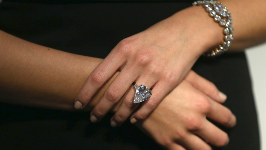 An assistant poses with a Star of Sierra Leone 968.9 carat diamond ring and a 7.13 carat diamond Cartier bracelet, during a sale preview at Christie's auction house in London, Britain October 20, 2016. (REUTERS/Neil Hall)