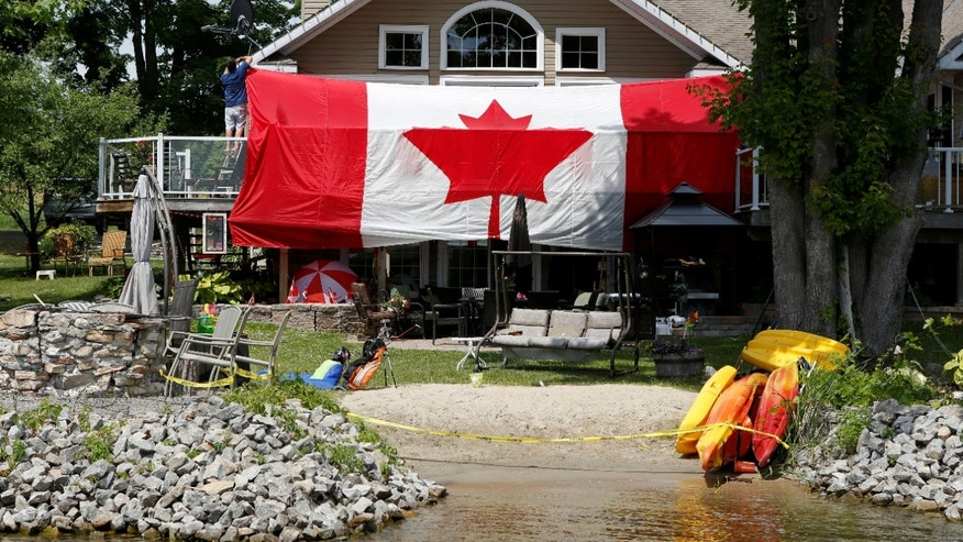A man hangs a large Canadian flag on the deck of his cottage to celebrate Canada Day on Big Rideau Lake in Rideau Ferry, Ontario, Canda July 1, 2016. (REUTERS/Gary Cameron)