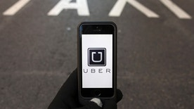 File photo - The logo of car-sharing service app Uber on a smartphone over a reserved lane for taxis in a street is seen in this photo illustration taken in Madrid on Dec. 10, 2014.