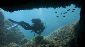 A scuba diver makes his way out from from an underwater passageway at Isola Bella in Taormina, Italy, at the start of summer holiday season on the Mediterranean isalnd of Sicily July 5, 2015.   REUTERS/John Schults  - RTX1J4JA