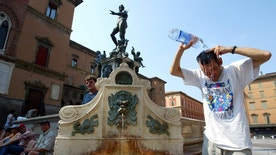 A tourist refreshes himself in front of the famous Neptune fountain in Bologna, central Italy, August 8, 2003. The temperature  reached one of its maximum levels in the north and central of Italy,  Italian weather forecasters said on Thursday. - RTXM4X9