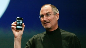 Apple Computer Inc. Chief Executive Officer Steve Jobs holds the new iPhone in San Francisco, California January 9, 2007. Apple unveiled an eagerly-anticipated iPod mobile phone with a touch-screen on Tuesday, priced at $599 for 8 gigabytes of memory, pushing the company's shares up as much as 8.5 percent. Jobs said the iPhone, which also will be available in a 4-gigabyte model for $499, will ship in June in the United States. The phones will be available in Europe in the fourth quarter and in Asia in 2008.  REUTERS/Kimberly White (UNITED STATES) - RTR1L0Z0