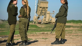 Israeli soldiers stand in front of the launcher of an Iron Dome missile interceptor battery deployed in the southern Israeli coastal city of Ashkelon January 16, 2014. Israel's Iron Dome missile defence system intercepted five rockets fired at the city of Ashkelon from the Gaza Strip on Thursday, and the military responded with a series of air strikes on the Hamas-controlled territory. REUTERS/Amir Cohen (ISRAEL - Tags: POLITICS CIVIL UNREST MILITARY CONFLICT) - RTX17GI3