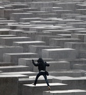 An unidentified youth jumps from one pillar to another at the Holocaust memorial in Berlin, March 3, 2010. The memorial to the murdered Jews of Europe consists of 2,711 charcoal-grey rectangular pillars, which rise from the ground and form a tight grid through which visitors can wander.     REUTERS/Tobias Schwarz     (GERMANY - Tags: SOCIETY) - RTR2B5WU