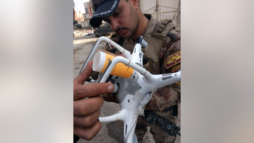 Iraqi Counter Terrorism Service solider in Mosul examines an ISIS drone modified to carry a 40mm rifle grenade in the attached plastic tube. Grenade is dropped when the drone is over Iraqi forces. (Mitch Utterback)