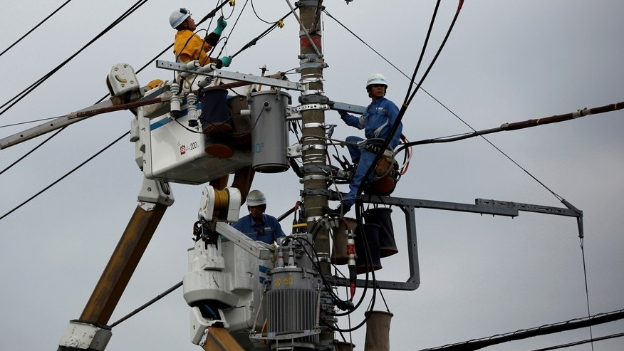 File photo--Men work around an electric utility pole along the street in Urayasu, east of Tokyo October 9, 2014. (REUTERS/Issei Kato/File Photo)