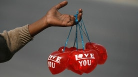 A boy holds Valentine's Day balloons for sale along the roadside in Lahore 