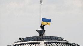 A climber installs the Ukrainian national flag on a roof, marking the Day of the State Flag, on the eve of the Independence Day, in Kiev, Ukraine, August 23, 2016.  REUTERS/Gleb Garanich - RTX2MNGB