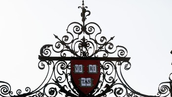 Harvard's seal sits atop a gate to the athletic fields at Harvard University in Cambridge, Massachusetts September 21, 2009.   REUTERS/Brian Snyder    (UNITED STATES) - RTR285O8