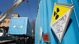 Workers place a container with spent highly-enriched uranium on a truck at a nuclear research facility in Kiev March 24, 2012. A consignment of enriched uranium - enough to make a nuclear weapon, U.S. experts said - rumbled out of a Ukrainian railway depot late on Saturday night bound for Russia, handing a success to an international summit on nuclear security.