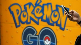 A man uses a mobile phone in front of an advertisement board bearing the image of Pokemon Go at an electronic shop in Tokyo, Japan, July 27, 2016.   REUTERS/Kim Kyung-Hoon - RTSJUQ0