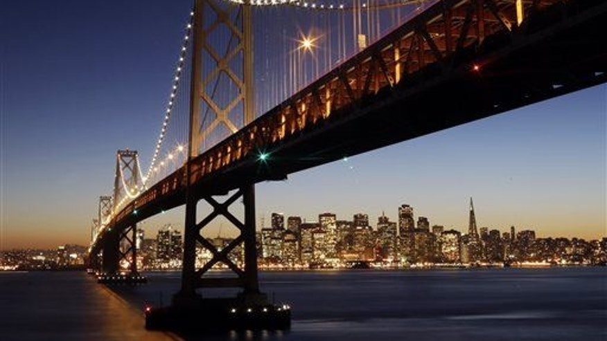 The San Francisco-Oakland Bay Bridge towers over the city skyline at dusk on Wednesday, Jan. 7, 2015, in San Francisco.