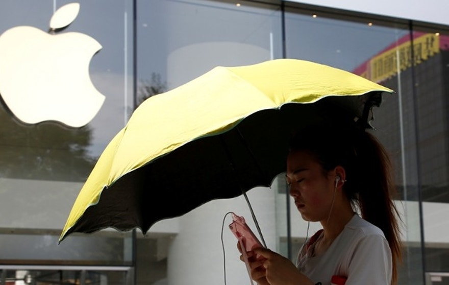 A woman uses a phone outside an Apple store in Beijing, China, July 27, 2016. REUTERS/Thomas Peter  - RTSJTJJ