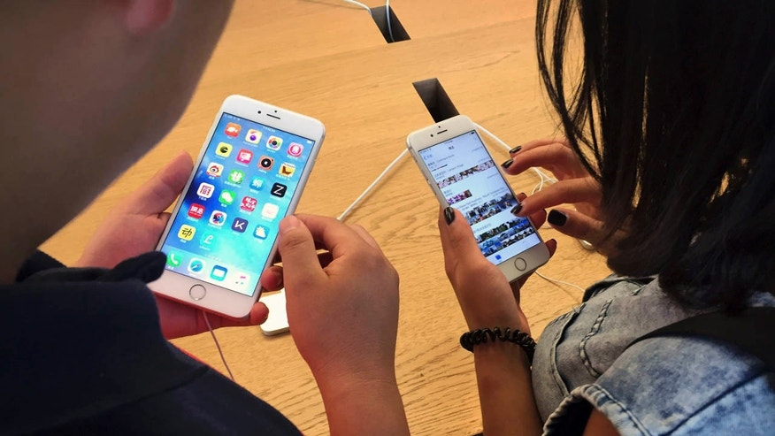 FILE - In this Saturday, June 18, 2016, file photo, customers try out Apple iPhone 6s models on display at an Apple Store in Beijing.