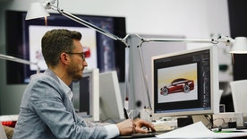 A man works in a showcase design studio at the fringes of a launch ceremony presenting the new Volkswagen Passat at the Volkswagen Design Center in Potsdam July 3, 2014. Volkswagen is steering the Passat upscale, aiming to lift its No.2 selling model clear of a struggling market for mid-priced cars without alienating its core family customers. At about 26,000 euros ($35,500), it will be priced only slightly above the current version, a company source said, but come in below BMW's 3-Series at 29,350 euros and the Mercedes-Benz C-Class at 33,558 euros.   REUTERS/Thomas Peter (GERMANY - Tags: TRANSPORT BUSINESS) - RTR3X10C