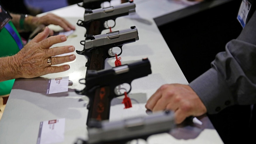 Guns sit on display at the NRA annual convention where President Donald Trump is scheduled to speak later in the day in Atlanta, Friday, April 28, 2017. (AP Photo/David Goldman)