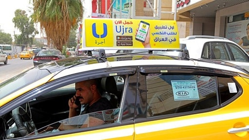In this Monday, May 1, 2017 photo, Ali Raad, a taxi driver who workes for the ride-hailing app Ujra, receives a call from a customer, in Baghdad, Iraq. Tech-savvy Iraqi entrepreneurs are finding success in creating companies that use smartphone apps inspired by such foreign businesses as food ordering and ride sharing. This comes at a time when the government is looking to the private sector to create more jobs. (AP Photo/Karim Kadim)