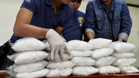 "Members of the Philippine National Police (PNP) get inventory of plastic bags containing methamphetamine hydrochloride known locally as ""shabu"", after they were seized in a police anti-drugs operation, at a police station in Manila, Philippines November 4, 2016. Picture taken November 4, 2016.  To match Special Report PHILIPPINES-DRUGS/CHINA     REUTERS/Ezra Acayan - RTX2VC3R"