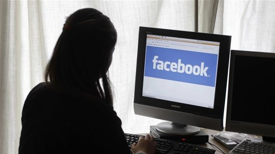 In this Monday, June 4, 2012, file photo, a girl looks at Facebook on her computer in Palo Alto, Calif.