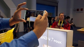 A man takes a photo with an Axon 7 Max smartphone with 3D camera at the ZTE booth during the 2017 CES in Las Vegas, Nevada January 6, 2017. REUTERS/Steve Marcus - RTX2XTVS