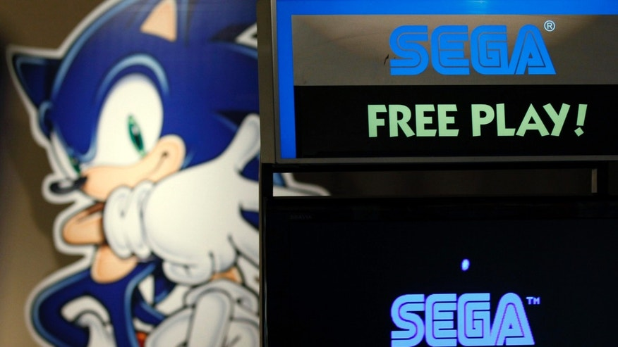 File photo: The Sonic the Hedgehog character is seen behind a video game screen showing a Sega Corp logo at a game arcade in Tokyo June 20, 2011.  (REUTERS/Kim Kyung-Hoon)