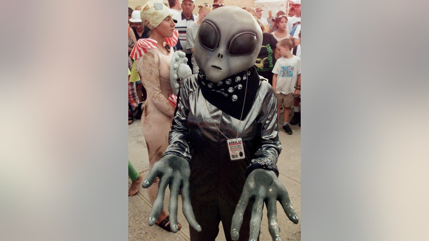 File photo - Crystal Graham, wearing an extra-terrestrial costume, waits in line for her turn in the UFO costume contest in Roswell, New Mexico. (Reuters)