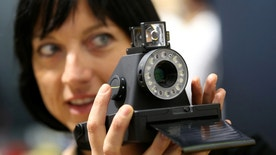 A woman takes a picture with the Impossible I-1 analog instant camera, the first new camera system working with the original Polaroid photo format, at the booth of the Impossible project on the Photokina, the world's largest fair for imaging in Cologne, Germany, September 20, 2016.       REUTERS/Fabrizio Bensch - RTSOK9Q