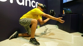 In this Friday, July 7, 2017, photo, Dennis Milman reaches to catch a virtual ball at the All-Star FanFest in Miami Beach, Fla. Virtual Reality baseball is a hit at the All-Star FanFest in Miami. Fans get to feel what it's like to be the San Francisco Giants' Buster Posey catching without the pain of snatching major league pitches at 86-to-93 mph. (AP Photo/Alan Diaz)