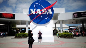 Tourists take pictures of a NASA sign at the Kennedy Space Center visitors complex in Cape Canaveral, Florida April 14, 2010. President Barack Obama will outline a revamped space policy on Thursday aimed at speeding development of a new heavy-lift rocket, increasing the number of human spaceflight missions, creating 2,500 new jobs and ultimately voyaging to Mars.  REUTERS/Carlos Barria (UNITED STATES - Tags: POLITICS SCI TECH) - RTR2CTIK