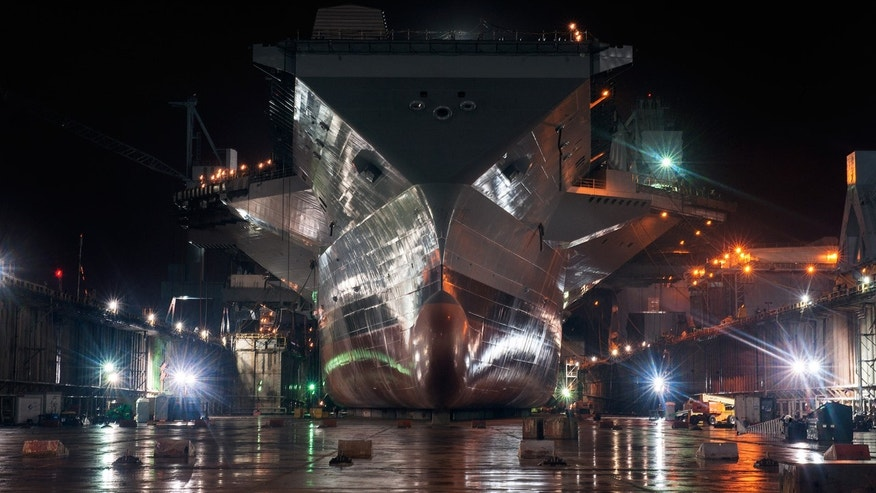 The freshly painted Gerald R. Ford shines at night in the empty dry dock waiting to meet water for the first time