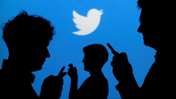 FILE PHOTO --  People holding mobile phones are silhouetted against a backdrop projected with the Twitter logo in this illustration picture taken in  Warsaw September 27, 2013.   REUTERS/Kacper Pempel/Illustration/File Photo - RTSR1PD
