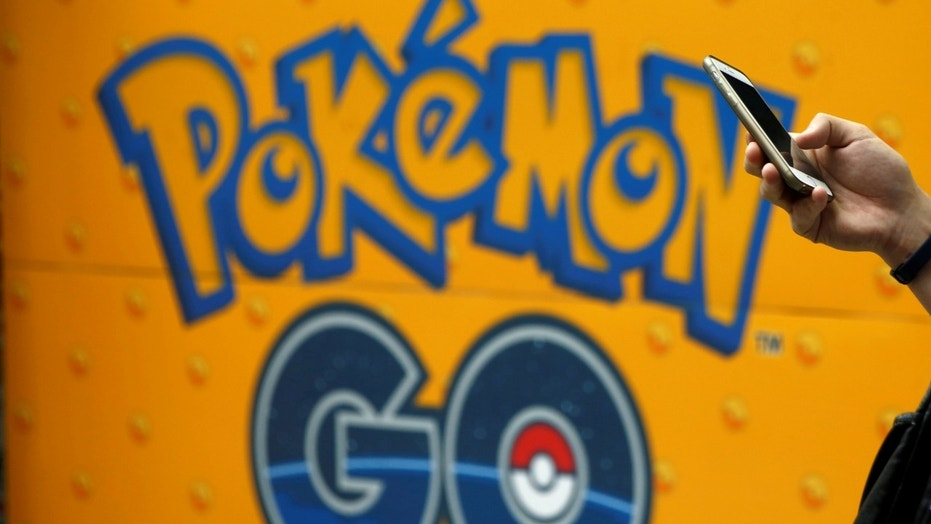 File photo: A man uses a mobile phone in front of an advertisement board bearing the image of Pokemon Go at an electronic shop in Tokyo, Japan, July 27, 2016. (REUTERS/Kim Kyung-Hoon)