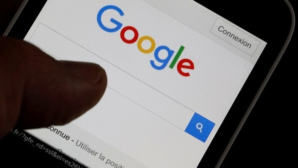 A man holds his smartphone which displays the Google home page, in this picture illustration taken in Bordeaux, Southwestern France, August 22, 2016. REUTERS/Regis Duvignau - RTX2MKPM