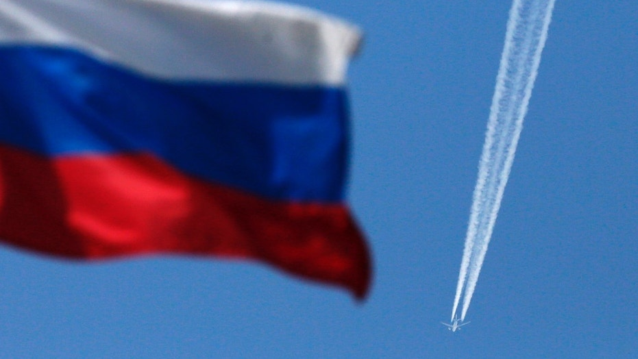 File photo - A contrail left by a passenger plane is seen behind a Russian state flag as it passes over the Siberian city of Krasnoyarsk, August 7, 2014. (REUTERS/Ilya Naymushin)