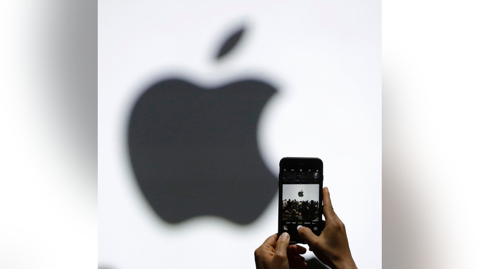 FILE - In this Monday, June 5, 2017, file photo, a person takes a photo of an Apple logo before an announcement of new products at the Apple Worldwide Developers Conference in San Jose, Calif. (AP Photo/Marcio Jose Sanchez, File)