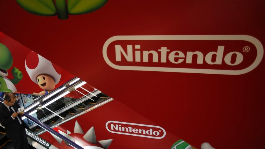 File photo: A shopper rides the escalator past Nintendo advertisements at an electronics retail store in Tokyo January 20, 2014. (REUTERS/Yuya Shino)