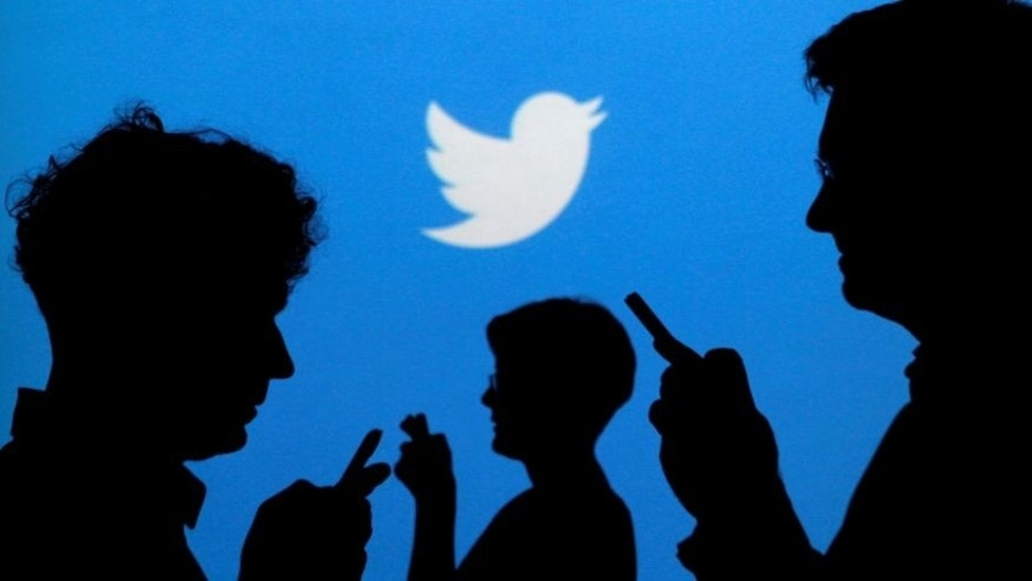 FILE PHOTO: People holding mobile phones are silhouetted against a backdrop projected with the Twitter logo in this illustration picture taken September 27, 2013. (REUTERS/Kacper Pempel/Illustration/File Photo)