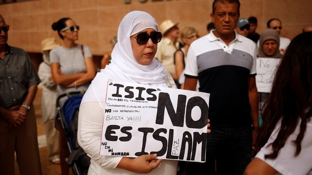 "A Muslim woman holds a sign that reads ""ISIS is not Islam"" as she takes part in a gathering of the Muslim, Christian and Jewish communities, in rejection to the attack at Las Ramblas in Barcelona earlier this week, in Fuengirola, southern Spain, August 20, 2017. REUTERS/Jon Nazca - RC13C8FE1630"